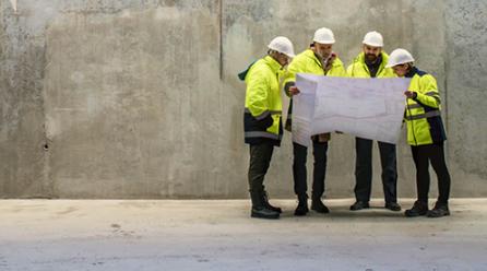 Groupe de d'hommes regardant un plan sur un chantier